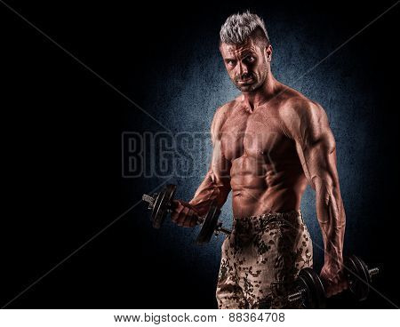 Portrait Of Aggressive Muscle Man Lifting Weights On Wall Background