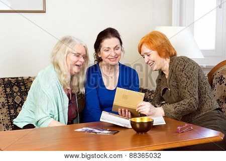Happy Women Looking At Their Old Photo In An Album