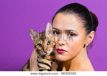 Woman with Bengal cat. Beautiful girl fashion beauty photography.