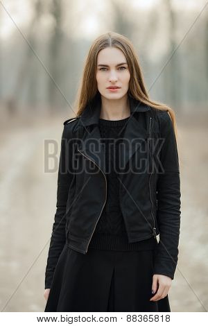 Outdoors portrait of young beautiful fashionable woman strolling at the evening in the forest park