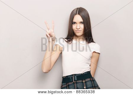 Young beautiful brunette woman posing indoors against wall with victory gesture