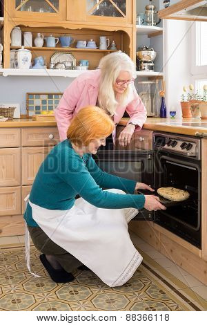 Mom Watching Other Mom Putting Cake In An Oven