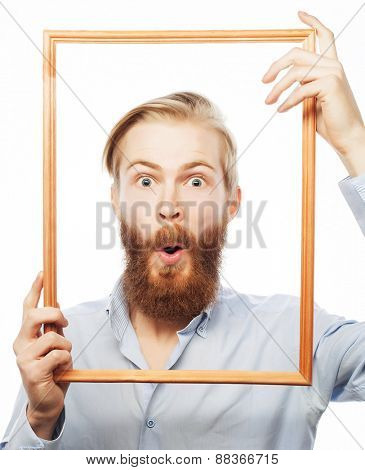 Funny picture. Young man wearing beard holding picture frame in front of his face and fun hamming, isolated on white.