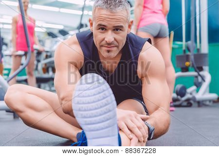 Man stretching and woman doing dumbbells exercises in gym