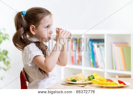 Cute kid girl drinking water in home
