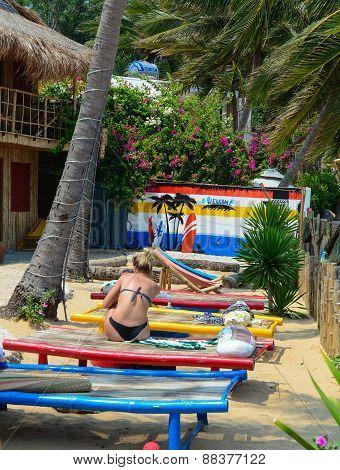 Tourists Sunbathing On Sand Of Beach