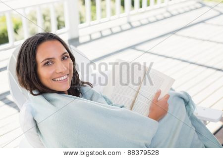 Pretty brunette sitting on a chair and reading a book in patio