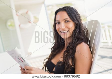 Pretty brunette sitting on a chair and reading magazine in patio