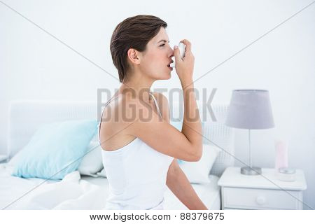 Pretty brunette taking her inhaler at home in the bedroom