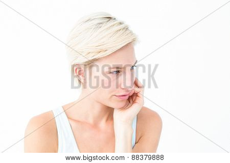 Thoughtful blonde looking away with hand on cheek on white background