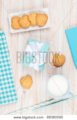 Cup of milk, heart shaped cookies, gift box and notepad on white wooden table with copy space