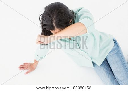 Sad woman sitting on the floor and hiding her face on white backgroung