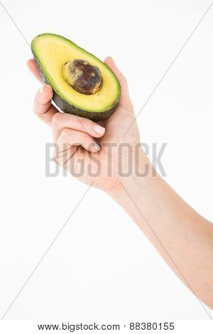 Woman holding half of an avocado on white background