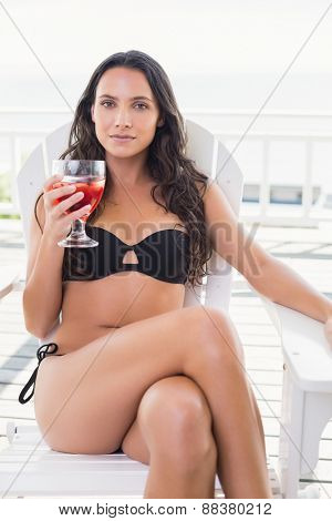 Pretty brunette sitting on a chair and drinking cocktail in patio