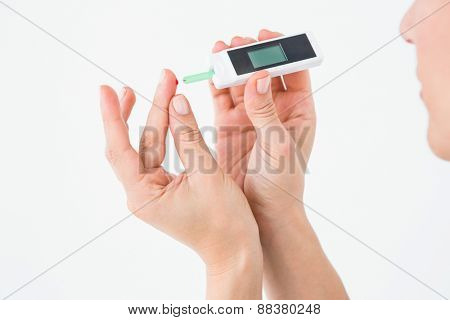 Diabetic woman using blood glucose monitor on white background