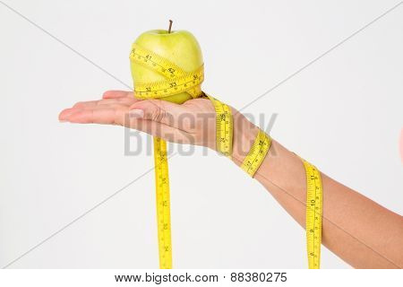Woman holding apple with measuring tape on white background