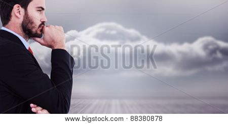 Thinking businessman standing with hand on chin against clouds in a room