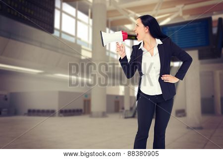 Pretty businesswoman shouting with megaphone against airport