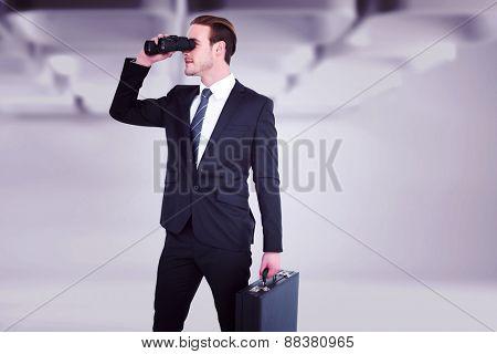 Businessman looking through binoculars against white abstract room