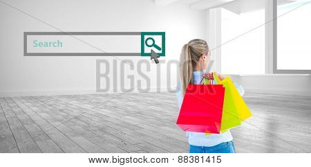 Pretty blonde holding shopping bags against white room with windows
