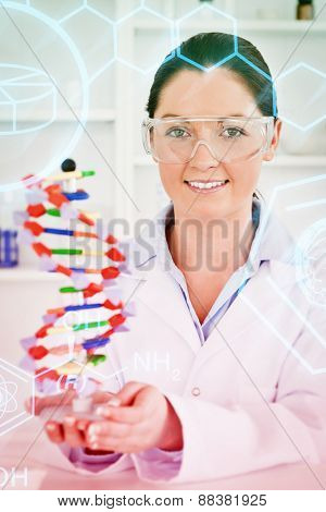 Science and medical graphic against portrait of a cute scientist showing the dna double helix model