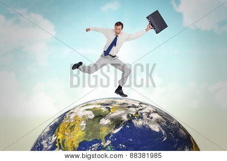 Cheerful jumping businessman with his suitcase against blue sky