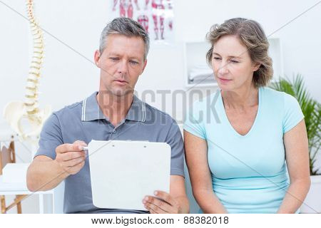 Physiotherapist reading his notes with his patient in medical office