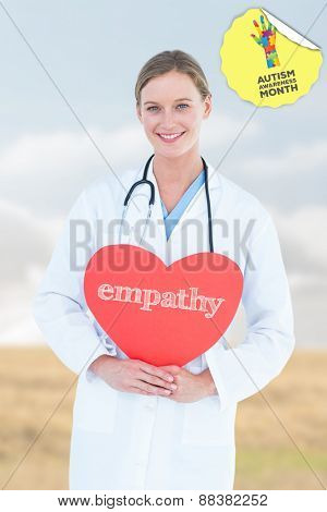 The word empathy and doctor holding red heart card against bright brown landscape