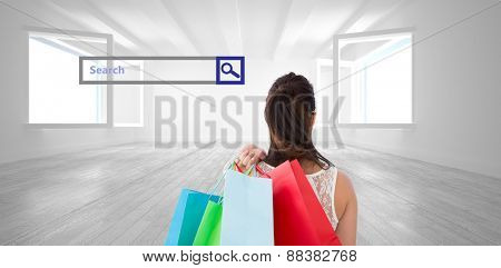 Rear view of brunette holding shopping bags against bright white room with opened windows