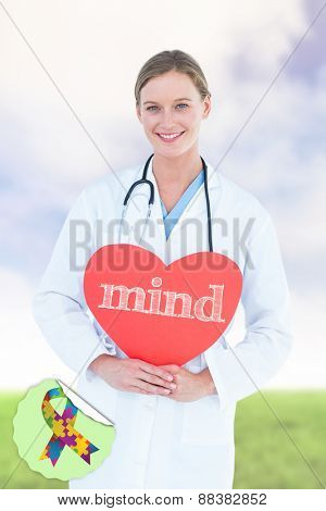 The word mind and doctor holding red heart card against green field