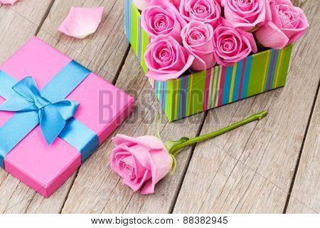 Valentines day card with gift box full of pink roses over wooden table