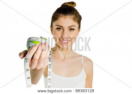 Slim woman holding apple and measuring tape on white background