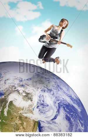 Pretty young girl playing her guitar against blue sky