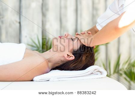 Brunette receiving forehead massage at the spa