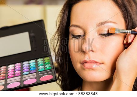 Work of make-up artist. Makeup artist apply makeup on the face of the girl model.