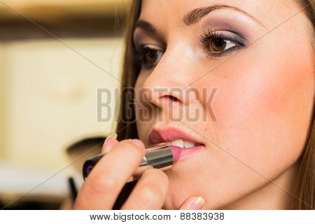 Work of make-up artist. Makeup artist apply lipstick on model.