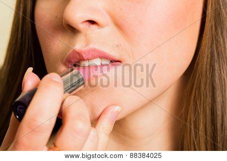 Work of make-up artist. Makeup artist apply lipstick on model.