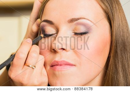 Work of make-up artist. Makeup artist apply eyeliner on girl model.