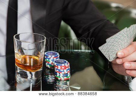 Poker player. Young guy in the casino at the gaming table. Man gambling, card games.