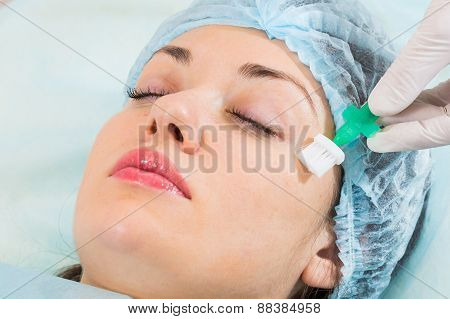 Young girl in a beauty parlor. Beautician spa facial treatment, a young girl