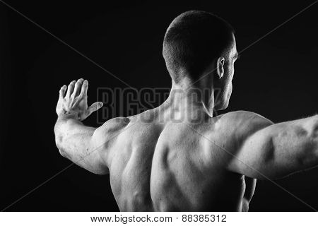 A strong man on a dark background. Bodybuilder showing muscles of the arms and back