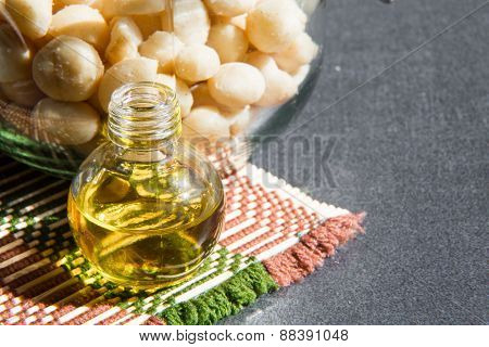 Still life with Macadamia oil in the bottle and nuts