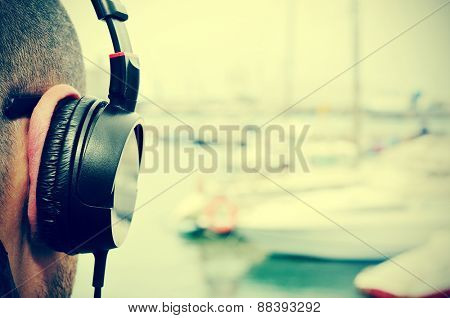 closeup of a young man listening to music with headphones in front of the sea in a marina, with a filter effect