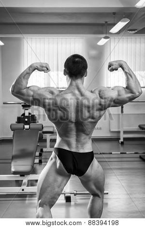 Bodybuilder man posing in GYM