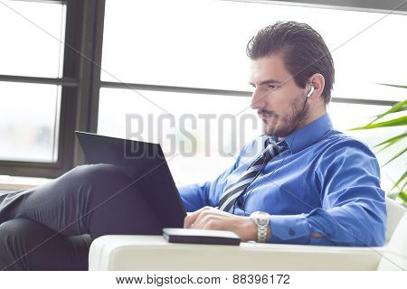 Businessman in office working on his laptop.