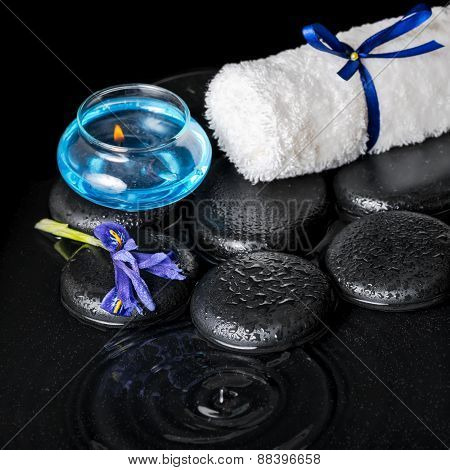 Beautiful Spa Concept Top Down Of Iris Flower, Blue Candle, White Towel And Black Zen Stones On Ripp