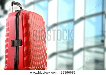 Red Plastic Travel Suitcase In The Airport Hall