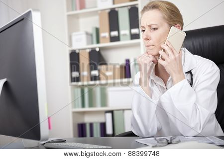 Woman Doctor Listening To Someone Over The Phone