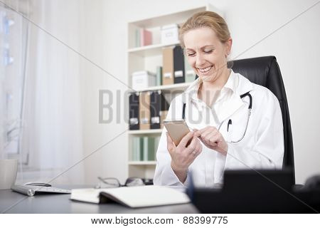 Happy Woman Physician Chatting At Her Mobile Phone