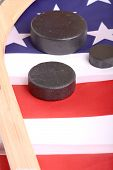 picture of inference  - Hockey equipment including a stick and puck on an American flag to infer a patriotic American sport - JPG